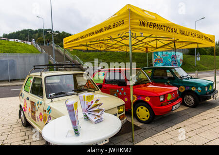 Bielsko-Biala, Poland. 12th Aug, 2017. International automotive trade fairs - MotoShow Bielsko-Biala. Three fiat 126p (polish - 'maluch') painted in flowers parked under yellow umbrella and promoting an international rally for save the bees. Credit: Lukasz Obermann/Alamy Live News - Stock Image