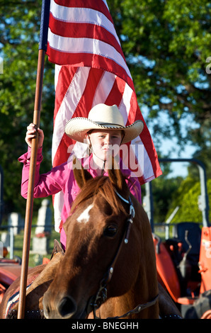 Cowgirl waving American flag  at PRCA rodeo event in Texas, USA - Stock Image