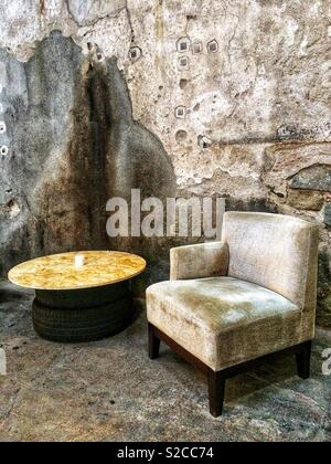 An old and vintage armchair and table in an old industrial building - Stock Image