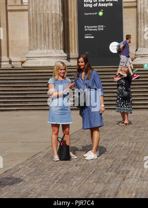 Two ladies look at photographs on their phone outside the British Museum, London, England - Stock Image