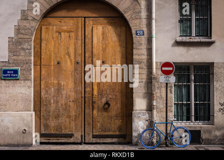 Bicycle by a traditional courtyard entrance in Paris, France - Stock Image