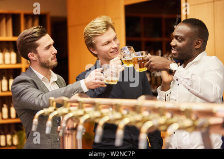 Men brag about having beer at the bar in a pub on a men's night - Stock Image