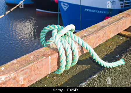 Rope tied to harbour rail Uk - Stock Image