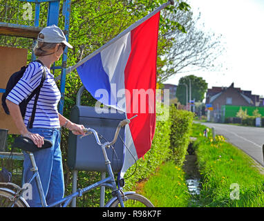 Female tourist standing with bicycle in front of Dutch flag in countryside at Rijnsburg,  Holland, the Netherlands - Stock Image