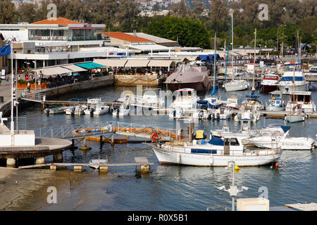Boats moored in Paphos Harbour. Restaurants on the quayside are full of tourists. Cyprus October 2018 - Stock Image