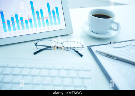 Image of workplace with electronic document, cup of coffee and eyeglasses on it - Stock Image