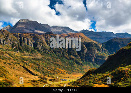 Autumn colors in Formazza valley in a sunny afternoon with mountains and cloudy sky in background - Stock Image