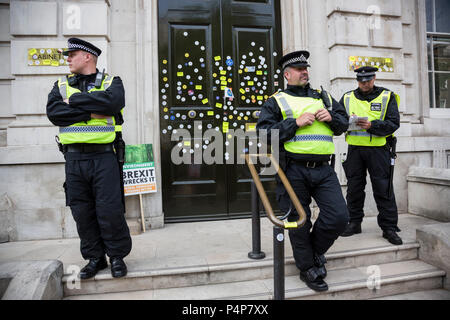 London, UK. 23 June 2018. Police officers guard the front door of the Cabinet Office from more defacement with stickers from remain supporters and protesters at an Anti-Brexit march and rally for the People's Vote. Photo: Bettina Strenske/Alamy Live News - Stock Image