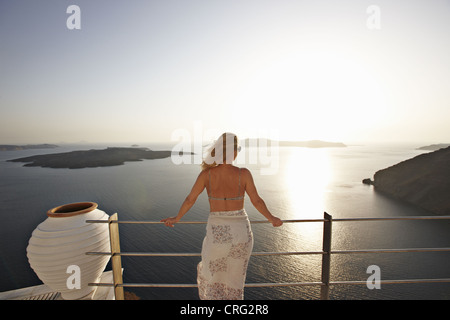 Woman admiring ocean view from balcony - Stock Image