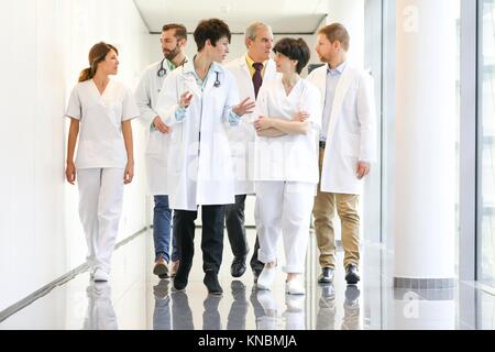 Doctors and nurses walking in corridor, Hospital - Stock Image