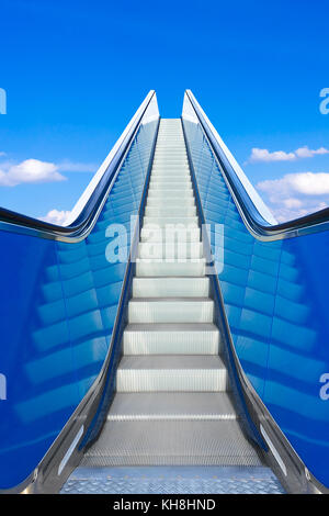 Escalator or moving stairs ascending into blue sky. Concept photo for success and climbing the job ladder. - Stock Image