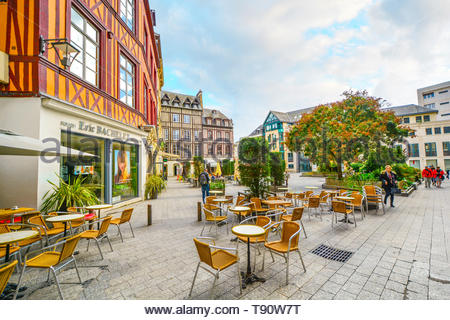 Timber frame homes line a town square in the medieval city of Rouen France with shops, a sidewalk cafe and tourists enjoying a sunny autumn day - Stock Image