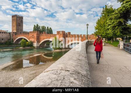 Woman walking on the riverfront in Verona. Castelvecchio bridge in background. Verona, Veneto, Italy - Stock Image