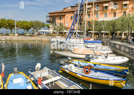 TORRI DEL BENACO, LAKE GARDA, ITALY - SEPTEMBER 2018: Sailing boats in the picturesque harbour in the town of Torri del Benaco on Lake Garda. - Stock Image