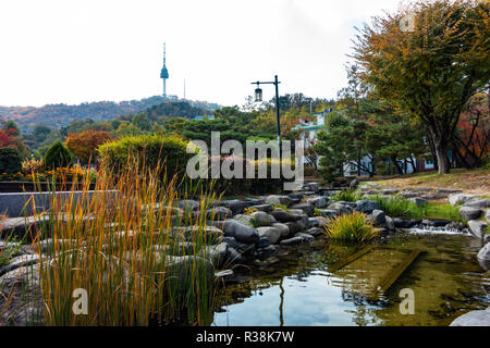 Namsan Tower seen from Namsangol Hanok Village, Seoul, South Korea. A beautiful garden and stream occupies the foreground with trees in autumn colours - Stock Image