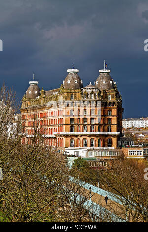 Scarborough's Grand Hotel, lit by strong afternoon sunlight stands out against a backdrop of gathering storm clouds. - Stock Image
