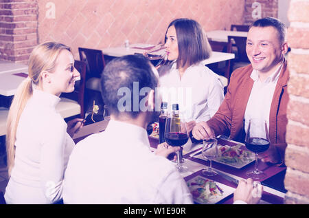 Happy company of friends eating delicious dinner in country restaurant - Stock Image
