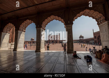 People relaxing under the shade of Jama Masjid mosque porches, Old Delhi, India - Stock Image