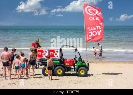 John Deere Gator transformed into ice cream truck selling ice creams to tourists on the beach at seaside resort along the North Sea coast - Stock Image