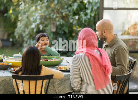Family eating dinner at table - Stock Image