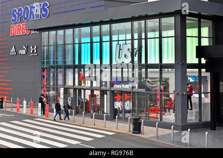 Dusk view of customers at Sports Direct store building entrance & glass shop front bollards protect from ramming retail park Thurrock Essex England UK - Stock Image