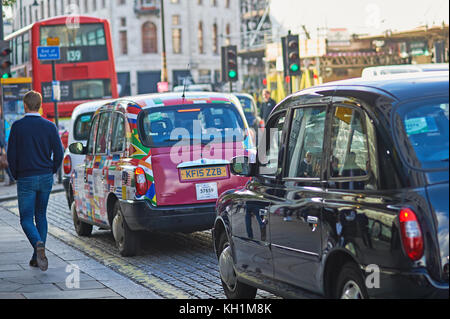 A man walking past a line of iconic London taxis waiting in the street. - Stock Image