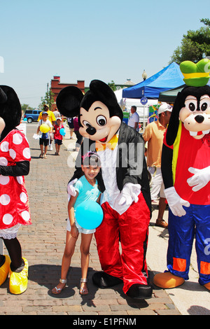 Disney Mickey Mouse, Goofy and Minnie Mouse interacting with small Hispanic girl at the International Festival in Arkansas. - Stock Image