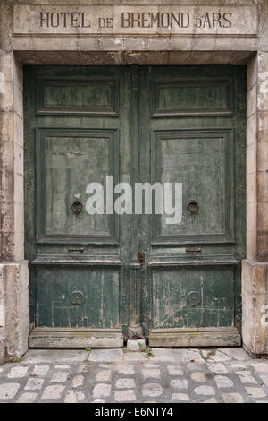 Old entrance to a hotel in France that is no longer open. What's behind the doors? - Stock Image
