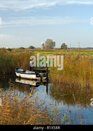 Boats moored in the narrow cut of West Somerton staithe, a remote part of the Norfolk Broads accessed via the River Thurne and Martham Broad. - Stock Image