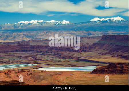 Behind the Rocks area and LaSal mountains seen from Dead Horse Point State Park, Utah. Potash evaporation ponds in the foreground. - Stock Image