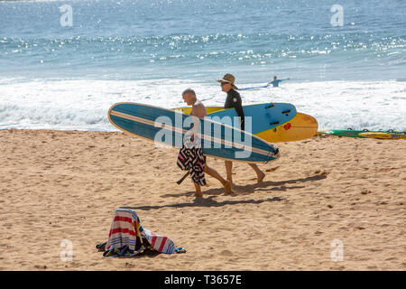 Two men walk on the sand at Palm beach carrying their surfboards longboards, Sydney,Australia - Stock Image