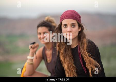 Two beautiful hippie girls at sunset - Stock Image