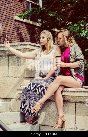 Two female university students sitting together on the campus taking a self-portrait with their smart phone and making silly pouty lips - Stock Image