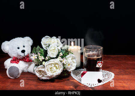 Beautiful bouquet of arranged flowers white candle on a holder, a hot glass of tea on a wooden table. mothers day, Easter, valentines, birthday, Chris - Stock Image