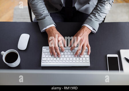 A midsection of businessman with computer sitting at the desk, working. A top view. - Stock Image