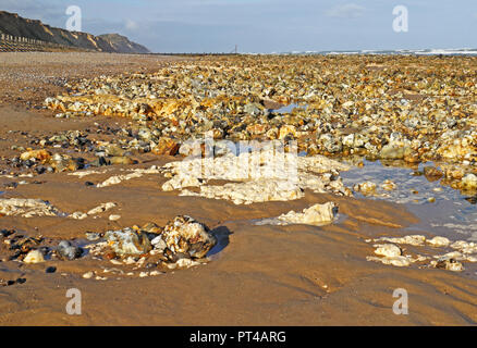 A view of a bed of flints and exposed chalk at low tide on the North Norfolk coast at West Runton, Norfolk, England, United Kingdom, Europe. - Stock Image