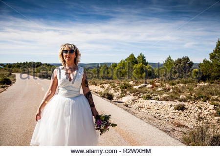 Bride with bouquet walks along a lonely road in a rural landscape - Stock Image