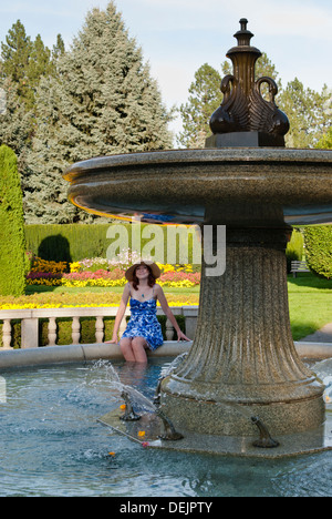 Pretty young woman cools off in the Davenport Fountain, Duncan Garden, Manito Park, Spokane, Washington State, USA. - Stock Image