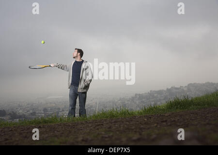 Young man with tennis racket, San Francisco, California, USA - Stock Image