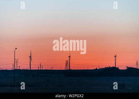 Snyder, USA view of wind turbine farm and power lines in Texas countryside industrial town and horizon with colorful red sunset - Stock Image