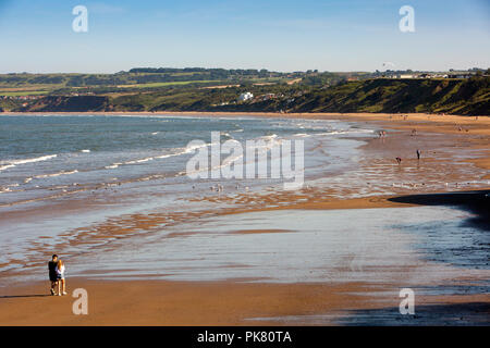 UK, England, Yorkshire, Filey, visitors walking on Muston Sands beach at low tide in sunshine - Stock Image