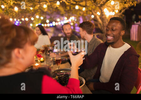 Happy friends toasting wine glasses, enjoying dinner garden party - Stock Image