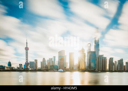 View Of Skyscrapers By River Against Cloudy Sky - Stock Image