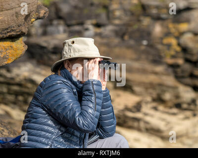 Adult woman wearing sunhat and padded puffer jacket looking through binoculars wildlife watching with rocky cliffs behind, Isle of Skye, Scotland, UK. - Stock Image