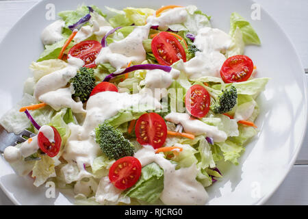 Plate of homemade fresh salad with buttermilk ranch dressing, tomatoes, broccoli, cabbage and carrots served over a white wooden table. House Salad. S - Stock Image