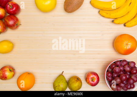Flat lay of arranged hazelnuts in word Health surrounded with plenty of healthy fresh fruit and gree on wood. - Stock Image
