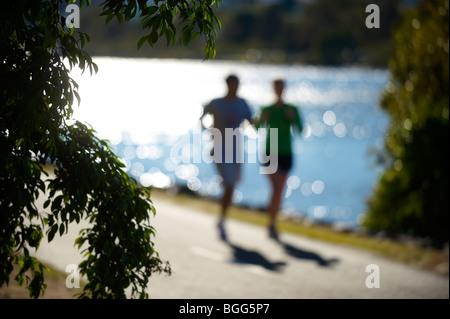Couple jogging beside Brisbane River Queensland Australia - Stock Image