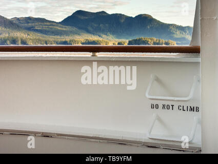 Metal ladder rungs on cruise ship deck with words 'do not climb', and view of mountain scenery in background, Inside Passage, near Ketchikan, Alaska. - Stock Image