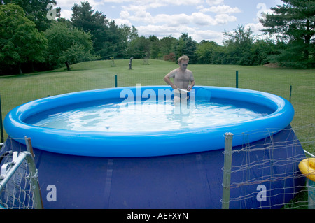 Ukrainian-American man cleans his pool in a suburban New Jersey town in the USA. - Stock Image