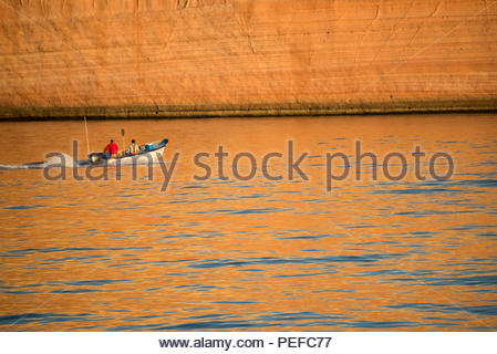A boat passes by the sandstone cliffs of Isla San Jose at sunrise. - Stock Image